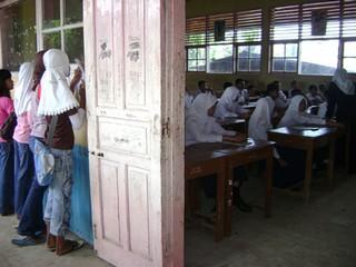 Seorang anak mendengarkan dan mencatat pelajaran sekolah di SMP 29 Padang